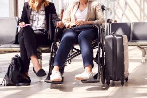שתי נשים ממתינות בשדה תעופה. אחת בכסא גלגלים